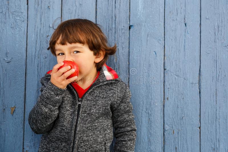 Little boy child kid eating apple fruit smiling healthy. Autumn royalty free stock photo