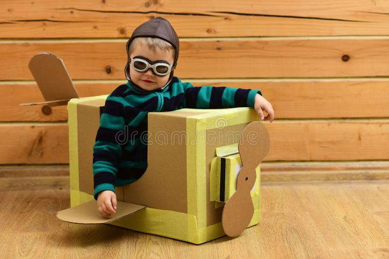Little boy child play in cardboard plane, childhood. stock photography