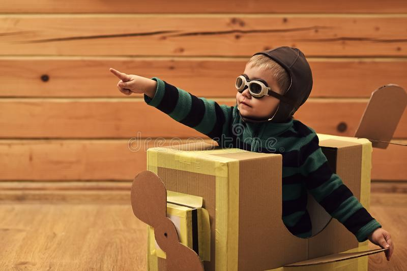 Little boy child play in cardboard plane, childhood. Dream, career, adventure, education. Kid, pilot school, innovation. Pilot travel, airdrome imagination Air stock photography