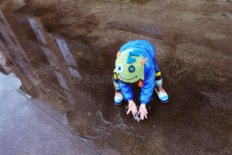 LITTLE BOY CHILD PLAYING WITH RAIN BOOTS BETWEEN BUILDINGS REFLECTIONS.  stock images