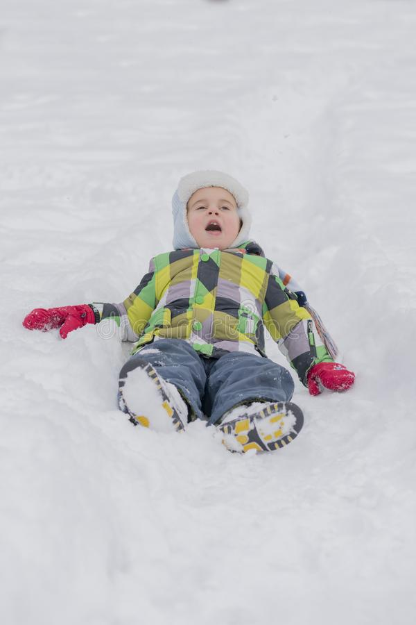 Little boy child playing with snow and having fun lying on snowy field and making snow angel outdoors in cold winter day. Children royalty free stock photography