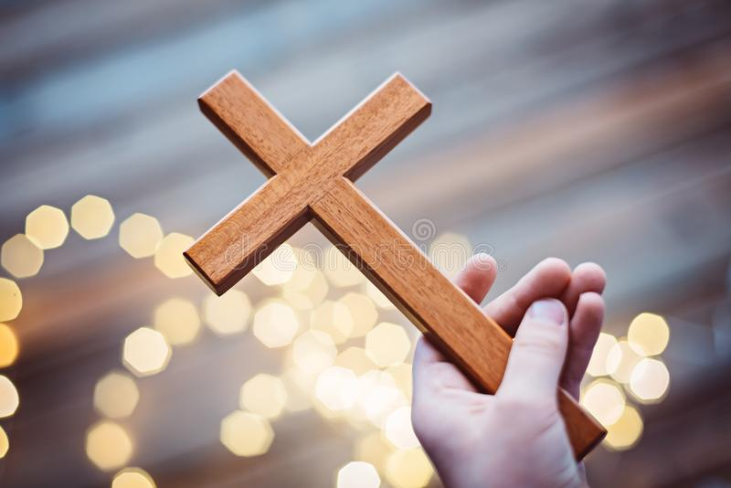 Little boy child praying and holding wooden crucifix stock photos