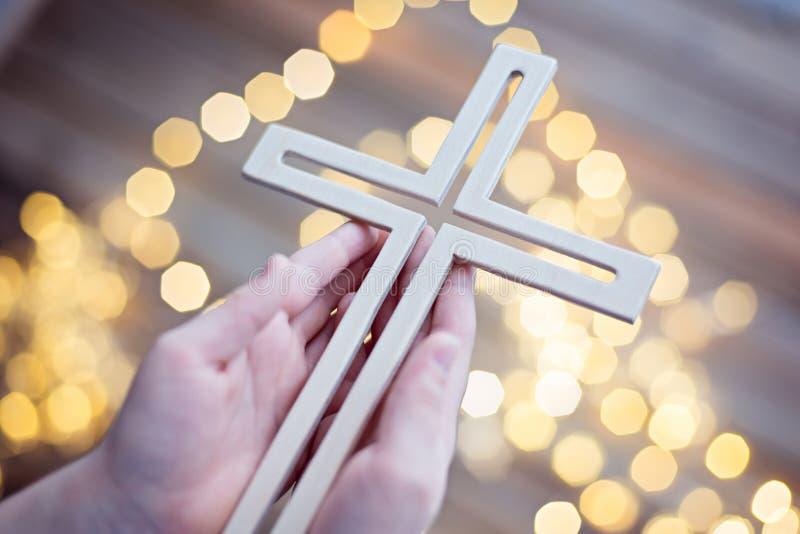 Little boy child praying and holding wooden crucifix stock photo