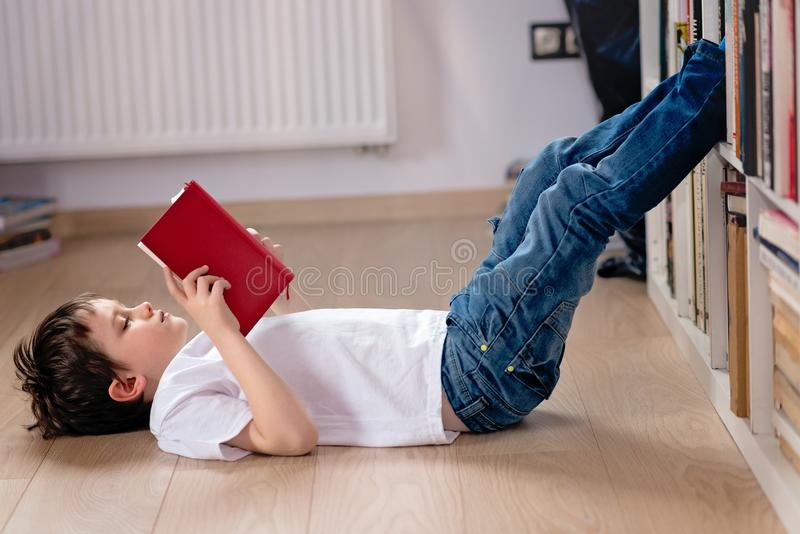 Little boy child reading a book in the library. He lies on the floor. Legs on bookshelf royalty free stock image