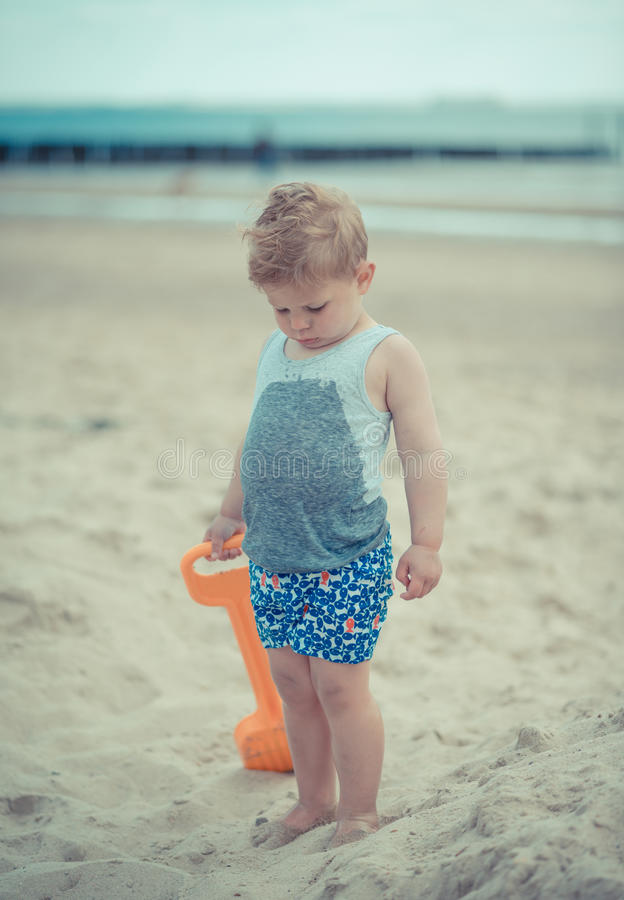 Little boy child standing with a wet shirt on the beach stock photo