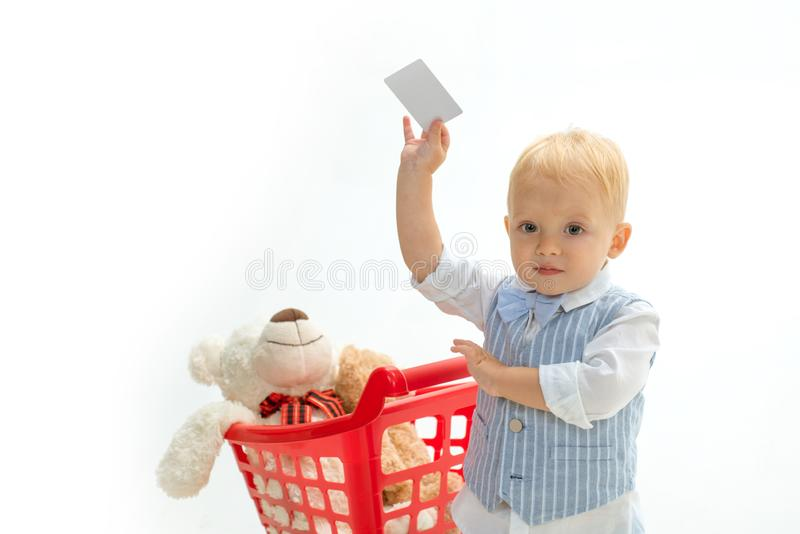 Little boy child in toy shop with credit card. savings on purchases. happy childhood and care. shopping for children royalty free stock images