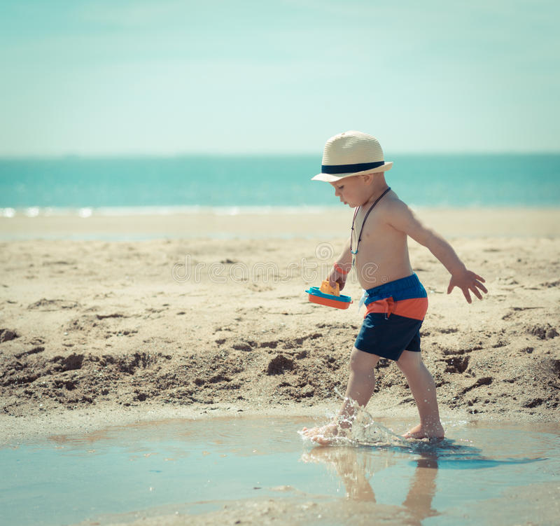 Little boy child walking on the beach inspecting a shell stock images