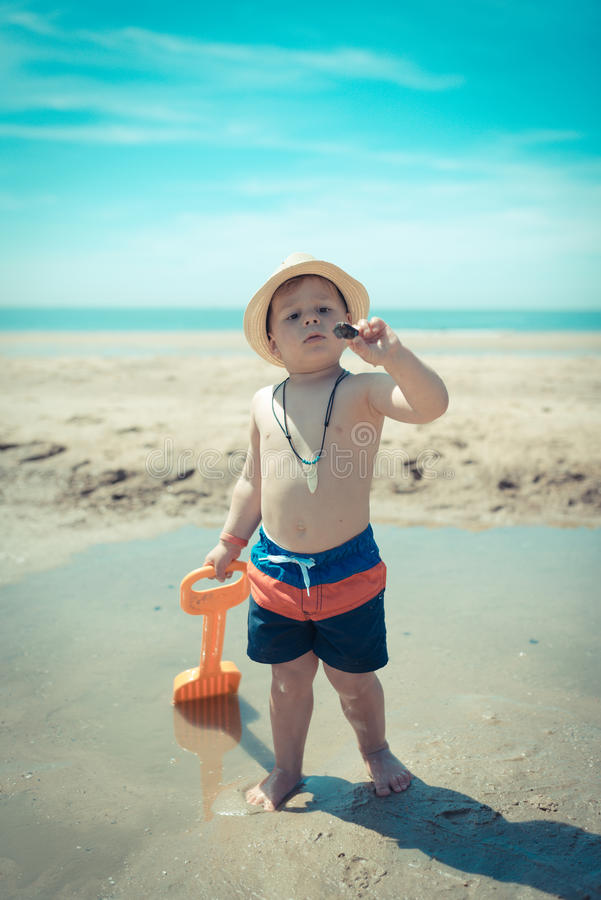 Little boy child walking on the beach inspecting a shell royalty free stock photo