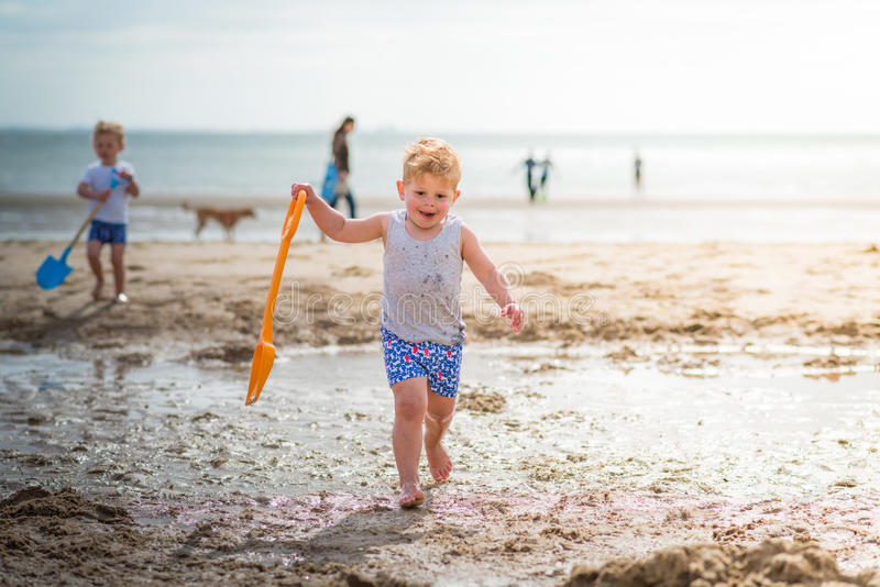 Little boy child walking on the beach with tongue royalty free stock images