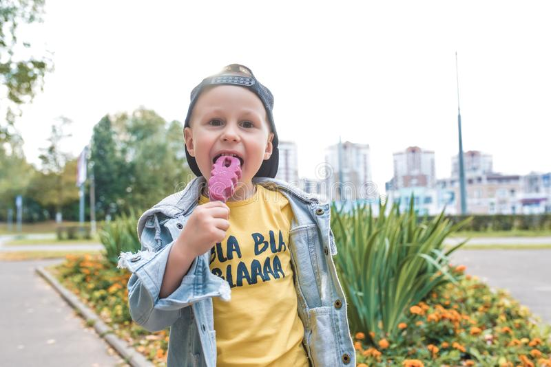 Little boy child 3-5 years old, happy smiling, laughing, eating pink ice-cream on stick, summer spring autumn day in royalty free stock photography