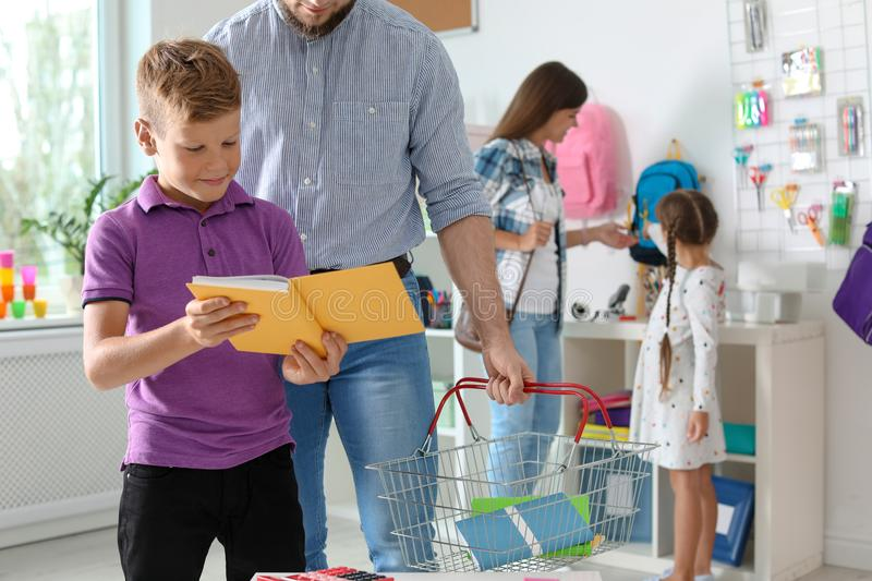 Little boy choosing school supplies with father royalty free stock image
