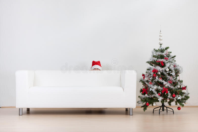 Little boy and Christmas tree. A little boy hiding behind the white couch and a Christmas tree stock photos
