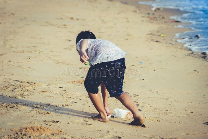 Boy is cleaning up garbage on the beach for enviromental clean up concept. Little boy is cleaning up garbage on the beach for enviromental clean up concept royalty free stock photo