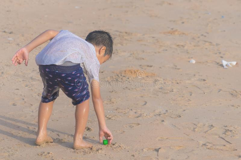 Little boy cleaning up garbage on the beach for enviromental clean up concept royalty free stock images