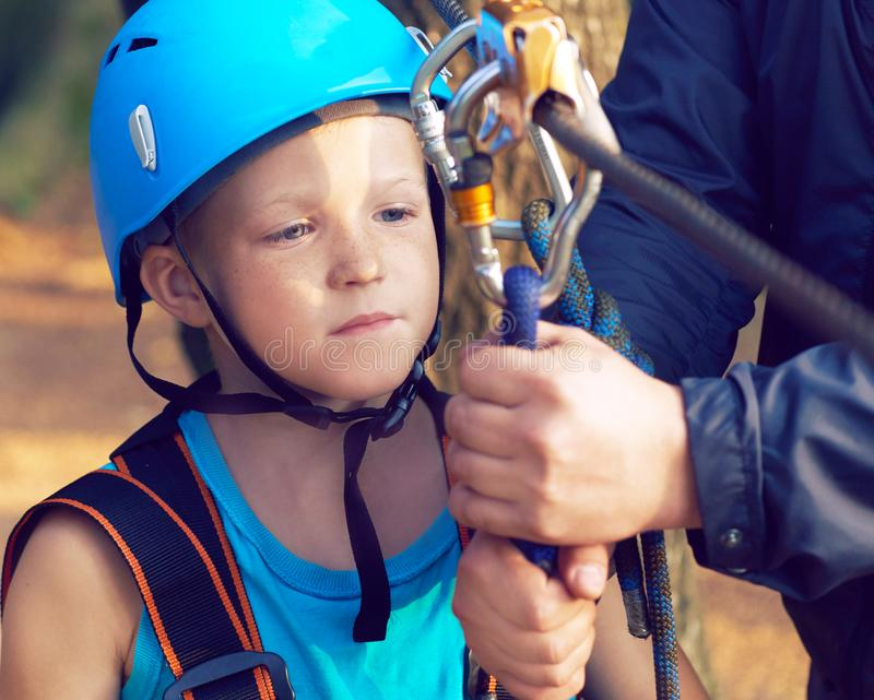 Cute little boy in blue shirt and helmet having fun at the adventure park, holding ropes and prepering to climb wooden. Little boy in climbing equipment and a royalty free stock photography