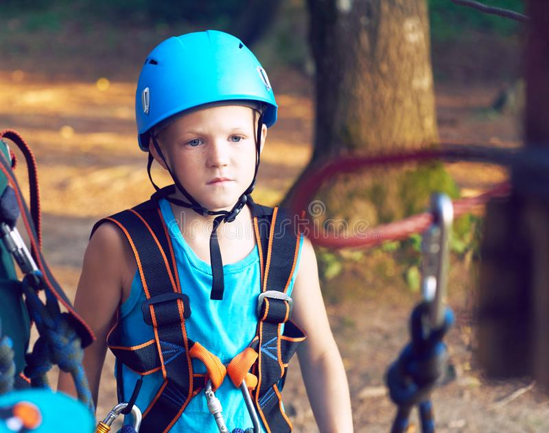 Cute little boy in blue shirt and helmet having fun at the adventure park, holding ropes and prepering to climb wooden. Little boy in climbing equipment and a royalty free stock photo