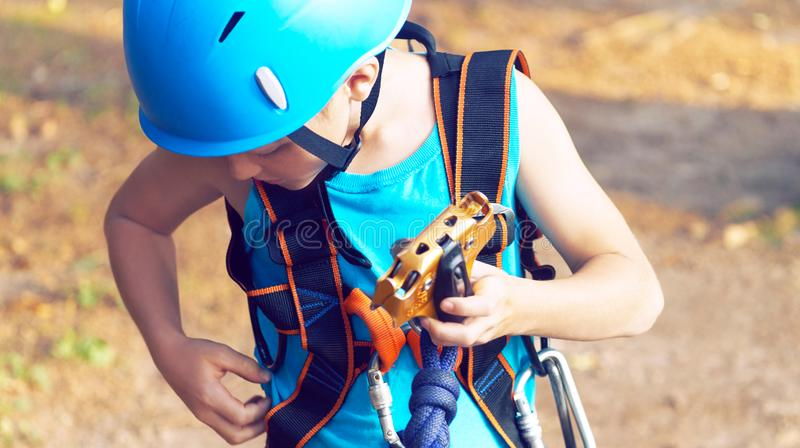 Cute little boy in blue shirt and helmet having fun at the adventure park, holding ropes and prepering to climb wooden. Little boy in climbing equipment and a royalty free stock images