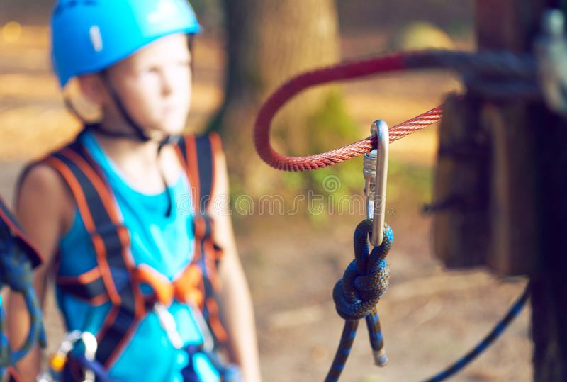 Cute little boy in blue shirt and helmet having fun at the adventure park, holding ropes and prepering to climb wooden royalty free stock photos