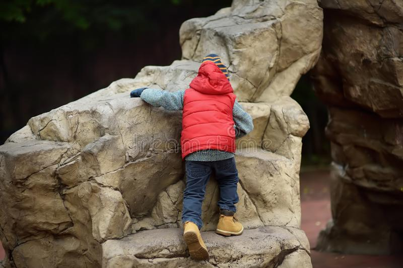 Little boy climbing on huge stone natural kids play ground. Outdoors activities for family with kids in spring/autumn stock photos