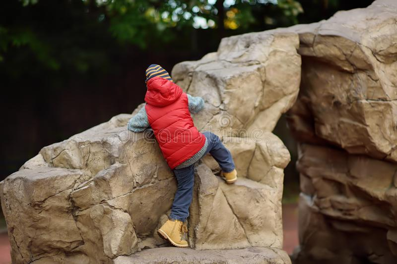 Little boy climbing on huge stone natural kids play ground. Outdoors activities for family with kids in spring/autumn stock photography