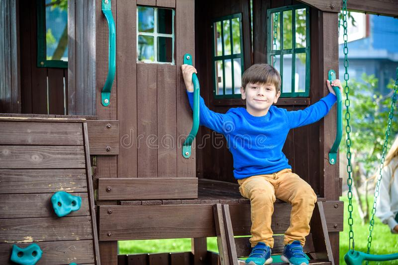 Little boy climbing ladder on slide at playground. Child is 5 7 royalty free stock photos