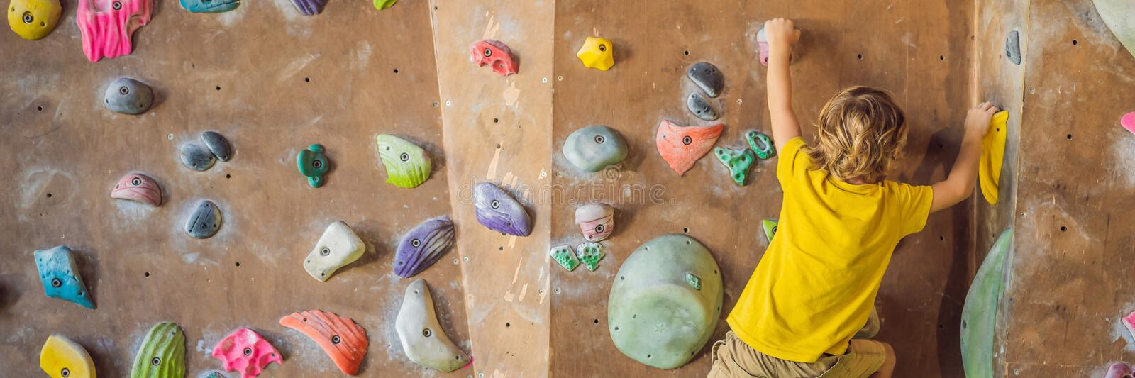 Little boy climbing a rock wall in special boots. indoor BANNER, LONG FORMAT stock images