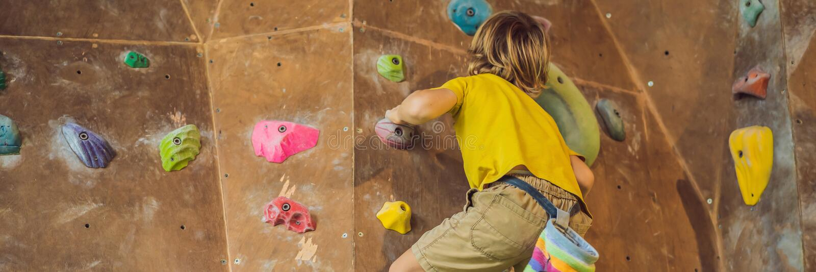 Little boy climbing a rock wall in special boots. indoor BANNER, LONG FORMAT royalty free stock photography