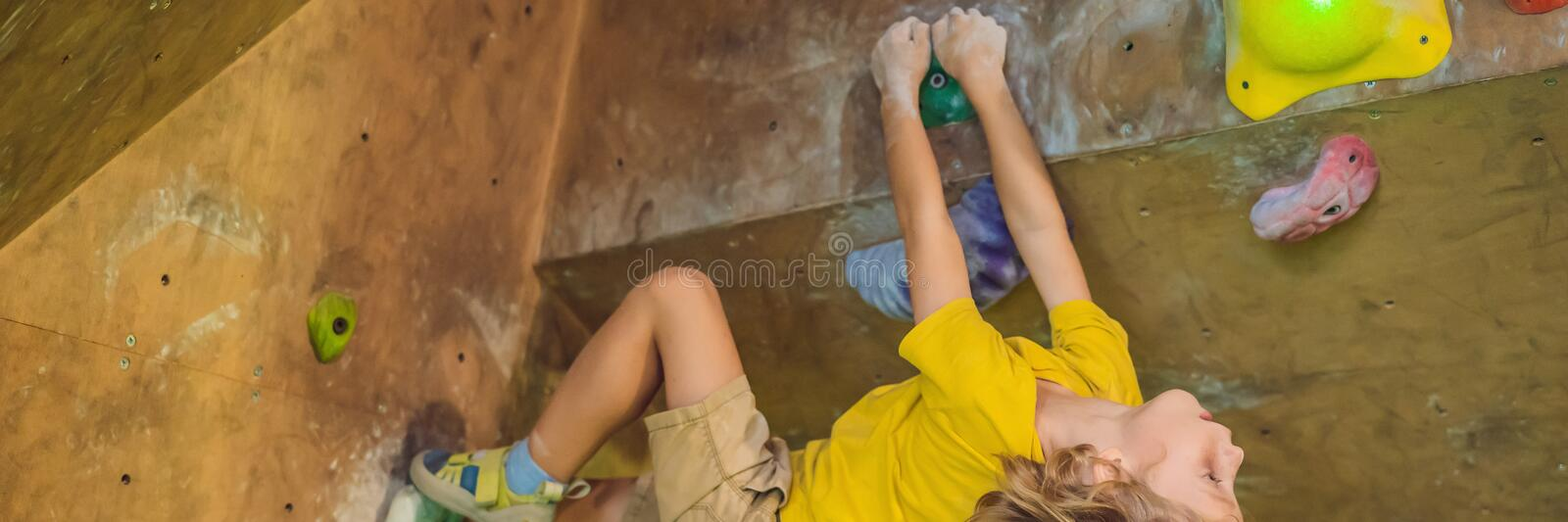 Little boy climbing a rock wall in special boots. indoor BANNER, LONG FORMAT stock image