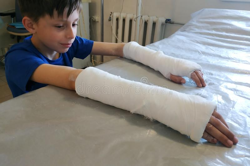 A little boy after a closed fracture approached the hospital for medical assistance in the form of an overlay of plaster bandage stock image