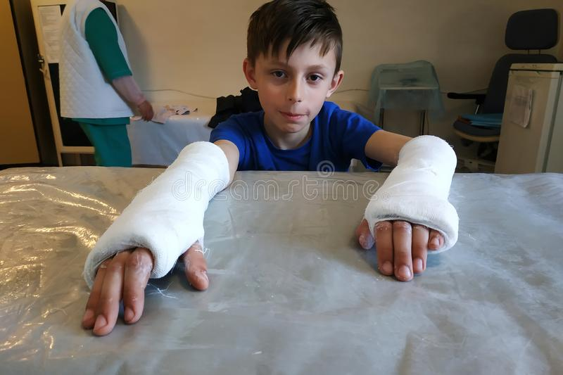 A little boy after a closed fracture approached the hospital for medical assistance in the form of an overlay of plaster bandage stock photos