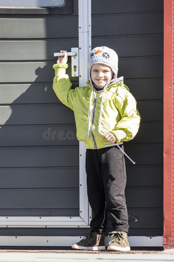Little boy in clothes and hat near the door. Portrait of boy in the yard outside. The child holds the door handle. stock photography