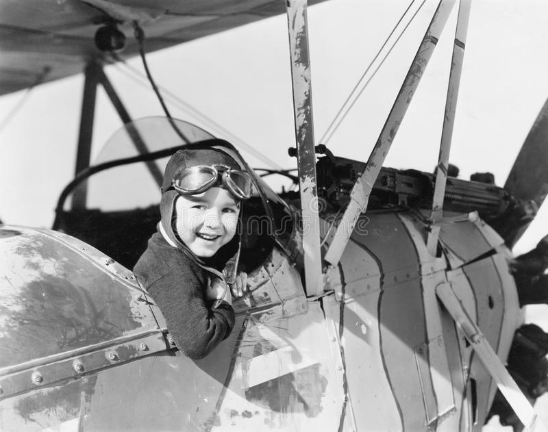 Little boy in cockpit of plane stock image