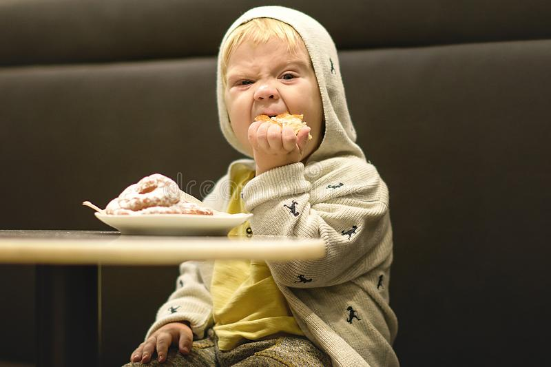 Little boy is eating the buns. royalty free stock photos