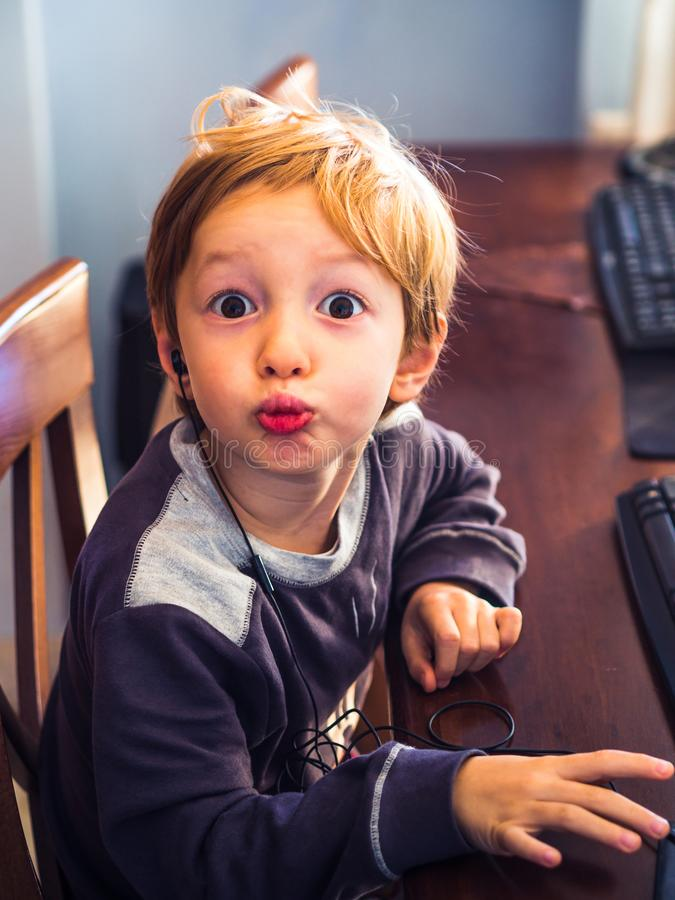 Little boy at computer with headset. Funny face royalty free stock images