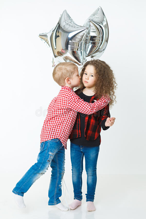 Little boy congatulate little curly girl,kiss, balloons. Studio. Fashion trendy clothes stock photo