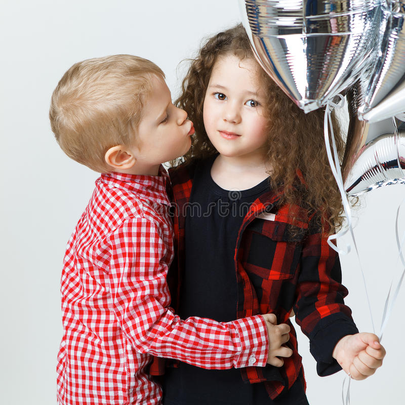 Little boy congatulate little curly girl,kiss, balloons. Studio. Fashion trendy clothes stock photos