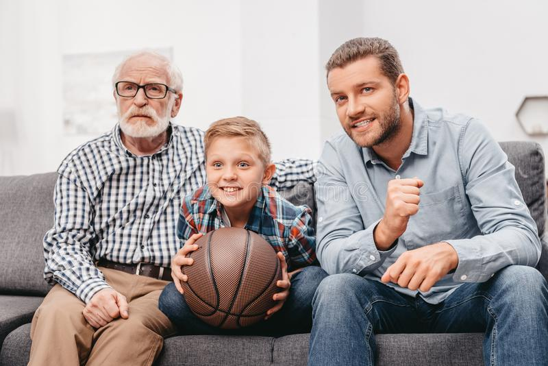 Little boy on couch with grandfather and father, cheering for a basketball game and holding a. Basketball ball royalty free stock photos