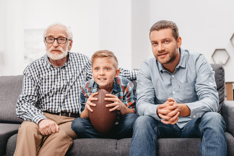 Little boy on couch with grandfather and father, cheering for a football game and holding a stock photography