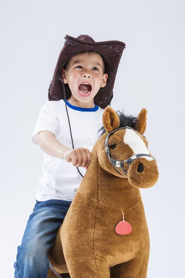Little Boy in cowboy Clothing Riding un cavallo simbolico della peluche immagine stock libera da diritti