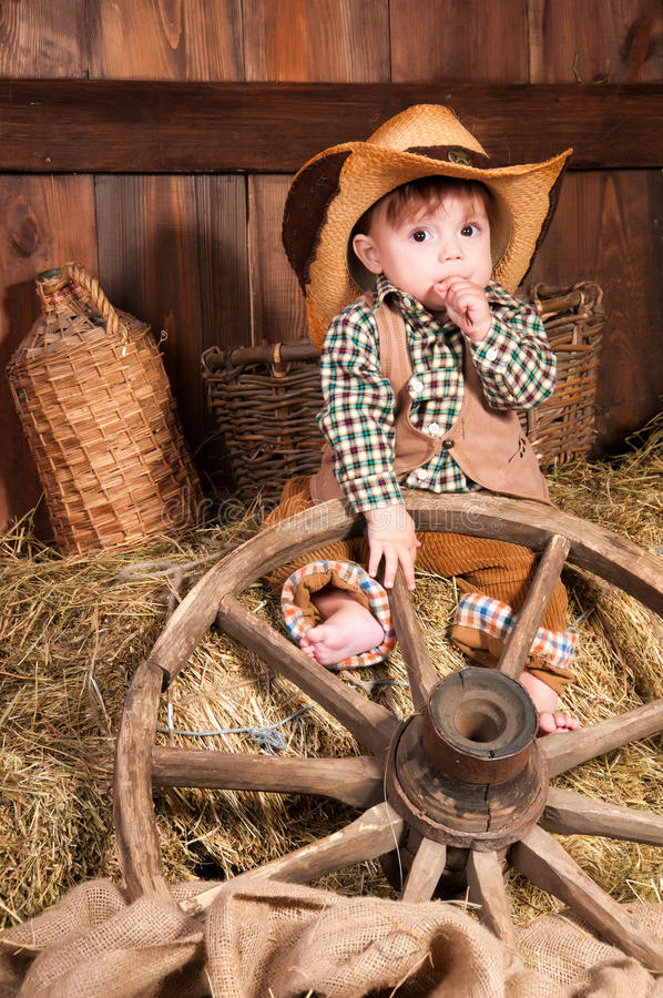 Little boy in cowboy hat, a waistcoat and a plaid shirt sitting in the hay stock images