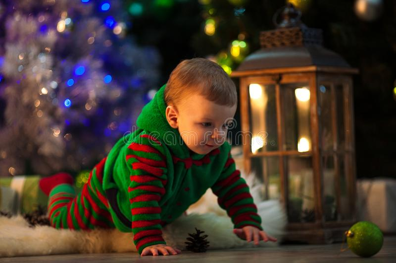 Little boy crawls to Christmas ball on floor near Christmas tree royalty free stock photography