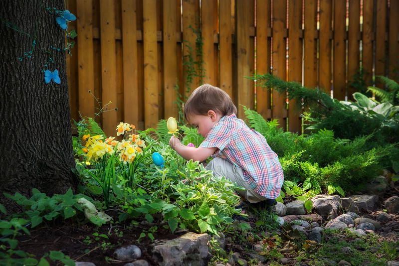 Little Boy Crouching Down Looking for Easter Eggs. A little boy crouched down looking for Easter eggs in a garden on an Easter egg hunt during the spring season royalty free stock image