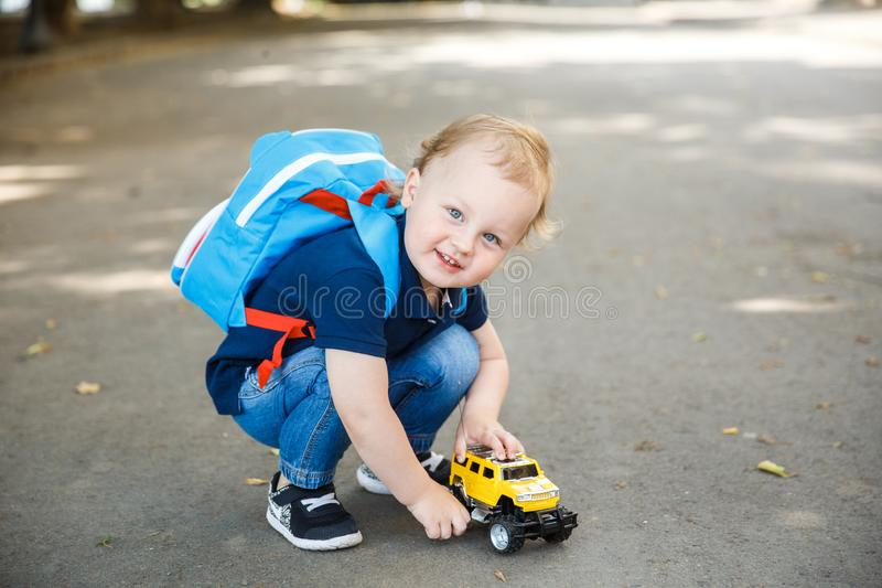 A little boy with curly blond hair is played with a toy car outside. He is looking at the camera and smiling. NnA little boy with curly blond hair is played with royalty free stock photo