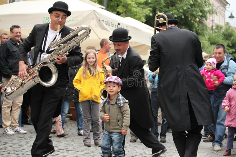 Little boy dancing with instrumentalists. Sibiu, Transyslvania Romania - May 28, 2012: Sibiu International Theatre Festival, the biggest performing arts festival royalty free stock photography