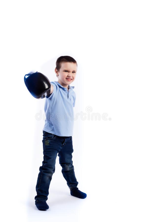 Portrait of happy joyful beautiful boy. A little boy with dark hair in blue jeans, a blue polo shirt in black and white boxing gloves is having fun, boxing and stock image