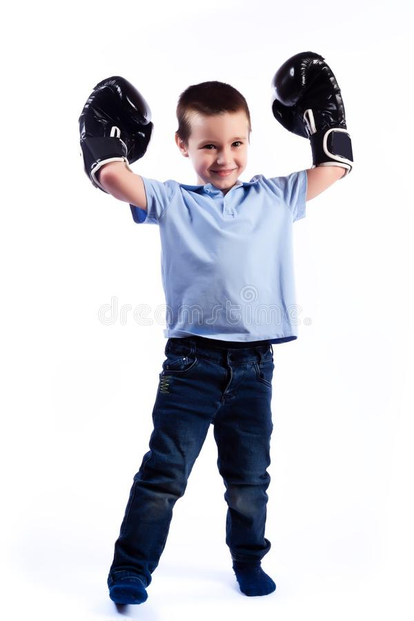 Portrait of happy joyful beautiful boy. A little boy with dark hair in blue jeans, a blue polo shirt in black and white boxing gloves is having fun, showing royalty free stock images