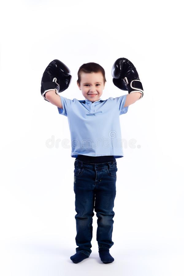 Portrait of happy joyful beautiful boy. A little boy with dark hair in blue jeans, a blue polo shirt in black and white boxing gloves is having fun, showing stock photo