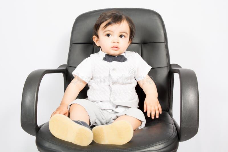 Little Boy, das als Geschäftsmann sitzt auf Schreibtisch im Büro vortäuscht stockfoto