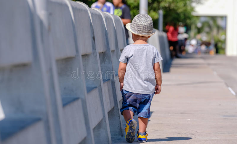 Little Boy, das auf die Brücke nahe Seeküste geht stockfoto