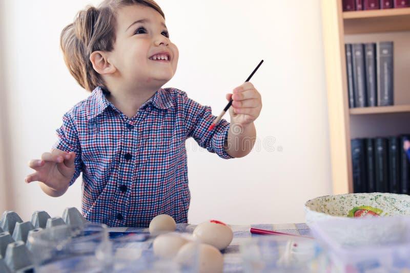 Little Boy, das mit Wasser-Farbmalenden Easter Eggs spielt lizenzfreie stockfotos
